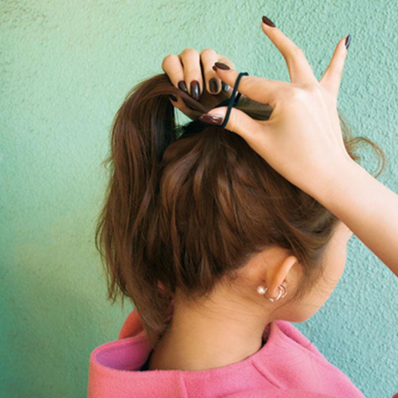 ②クリームを髪全体につけ、ざっくりと手でまとめて、高めのポニーテールに。