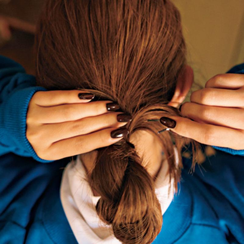 ④髪の毛先を一部とり、ゴムを隠すように巻きつけたら、ピンで留めます。